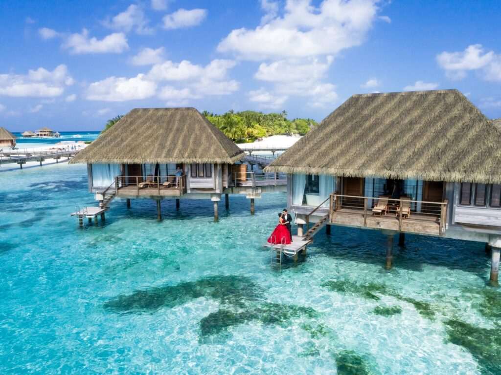 Couple on porch of over-water bungalow in the Maldives